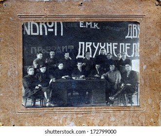USSR, UKRAINE, MARIUPOL - NOVEMBER 11, 1926: An antique photo shows a group of men - members fortnightly refresher courses, posing near the desk