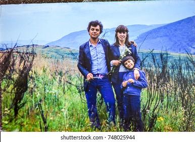 USSR, WESTERN UKRAINE, CARPATHIAN MOUNTAINS - CIRCA 1982: Vintage photo of parents with little son in mountain meadow field landscape in Western Ukraine, USSR