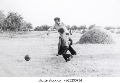 USSR, WESTERN UKRAINE, DOLISHNEE VILLAGE - CIRCA 1982: Vintage photo of dad and son playing football soccer in Western Ukraine, USSR