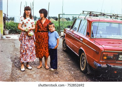 USSR, WESTERN UKRAINE, DOLISHNEE VILLAGE - CIRCA 1983: Vintage photo of young women with little boy in village courtyard at red car  in Dolishnee village, Western Ukraine, USSR