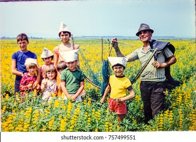 USSR, WESTERN UKRAINE, DOLISHNEE VILLAGE - CIRCA 1983: Vintage photo of group of kids with adult man on meadow yellow flowers landscape in Western Ukraine, USSR