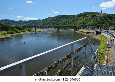 Usti nad Labem, Czech republic - June 30, 2018: train bridge over river Labe in czech city Usti nad Labem with locks on railing in foreground during summer day