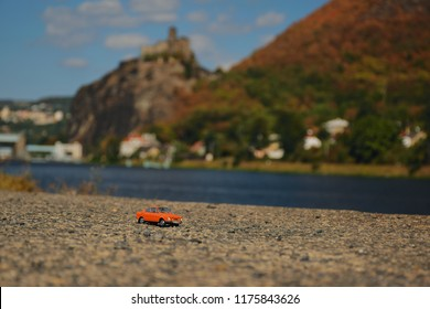 Usti nad Labem, Czech republic - September 08, 2018: orange model of legendary czechoslovak car Skoda 110R named Erko from year 1980 near Elbe river with Strekov castle on background afternoon