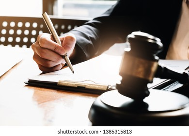ustice and Law concept. Legal counsel presents to the client a signed contract with gavel and legal law or legal having team meeting at law firm in background