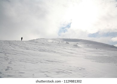 Ustrzyki Gorne, Poland - February 24, 2018: Man enters the mountains in winter. Mountain trail to Tarnica in winter. Bieszczady National Park in winter. Snow-covered trees and mountains.