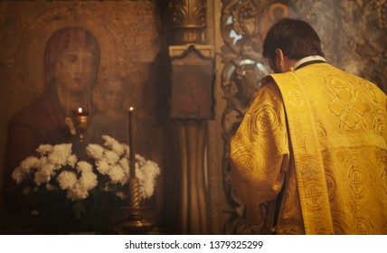 Ustyuzhna, Vologda region, Russia December 20, 2014 The deacon prays before the icon of the Mother of God in an Orthodox church.