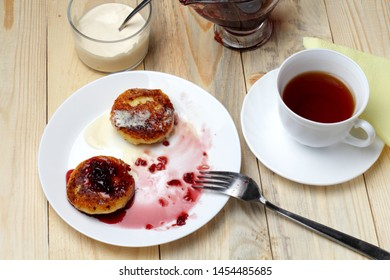 The usual breakfast in the village, fried pancakes from cottage cheese, blueberry jam, tea or milk. Background made of wood.