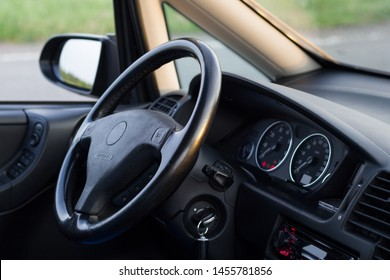 Usual car inside. Interior details of well maintained vehicle. View on steering wheel. Ignition key in the lock in On position. Dashboard lights indicate service icons. Backlight turned on.