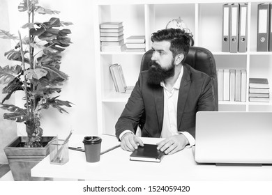 Usual day in office. Man bearded hipster boss sit in leather armchair office interior. Boss at workplace. Manager formal clothing corporate style working. Business people concept. Busy boss in office.