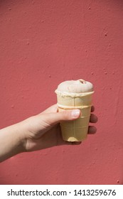 the usual waffle Cup of chocolate ice cream in hand on a red background isolated