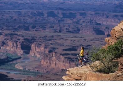 Utah,  USA- May 2002: A female mountain biker enjoying the views at Dead Horse Point, Utah, USA