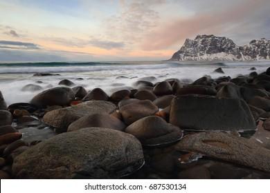 Utakleiv beach-northeastward view-background mounts lining the N.shore of Steinsfjorden: Medskolmen-Hogskolmen-Stirabben. Waves breaking on the shore boulders. Vestvagoya-Lofoten-Nordland fylke-Norway
