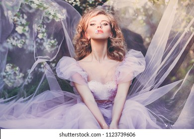 utdoors beauty close up portrait of beautiful young woman enjoying of blooming apple trees. Ball gown. Romantic mood. Charming. Apple tree flower in lips. Wearing light pink dress. Sensual