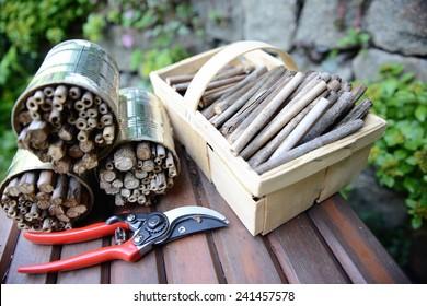 Utensilien zum Bau eines Insektenschutzbunkers für Wildbienen auf einer Bank. Gartenschere, Korb mit Holzstöcken.