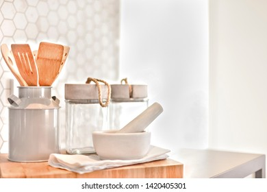 Utensils bottles and spoons on the wooden tray with an entrance which spreading the sunlight
