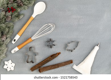 Utensils for Christmas cooking or baking with spoon, whisk, cookie cutter, icing piping bag, cinnamon sticks and snow flake, with fir branch over stone like background