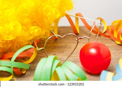 Utensils of a clown costume laying on a wooden board