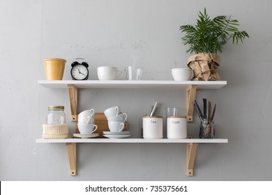 Utensils and mugs on shelf