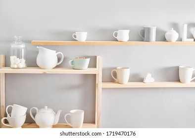 Utensils and mugs on shelf. Dishes in cupboard in kitchen. Kitchenware on wooden shelves. Kitchen interior background.Opened cupboard with kitchenware inside.