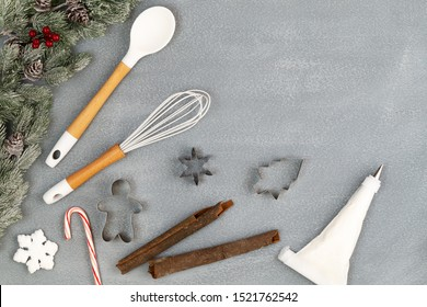 Utensils and spice for Christmas cooking or baking with spoon, whisk, cookie cutters, icing piping bag, cinnamon sticks, candy cane and snow flake over concrete background, copy space, top view.