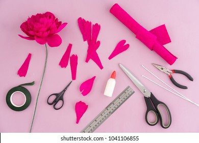 Utensils and tools for making crepe paper flowers on pink wooden background