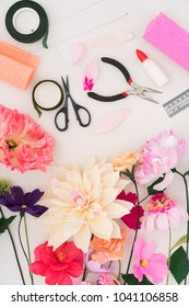 Utensils and tools for making crepe paper flowers on white wooden background