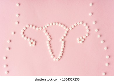 The uterus is laid out of tablets on a pink background. Space for text