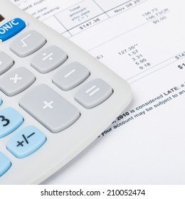 Utility bill with calculator over it - 1 to 1 ratio