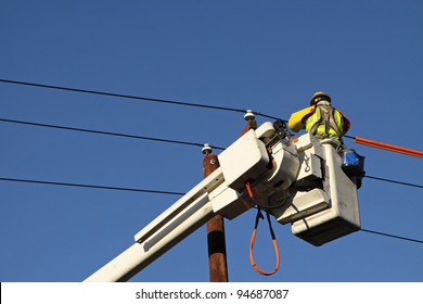 Utility Lineman Working on Cables Against Blue Sky