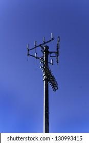 Utility pole against a deep blue sky.