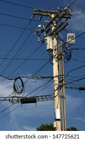 A utility pole with many wires and items using the pole