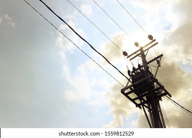 Utility pole supporting overhead power line cables against blue sky as copy space