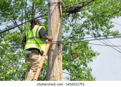 Utility pole worker installs new cables on an electric post using 40ft ladder