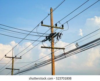 Utility poles supporting wires for various public utilities on blue sky background
