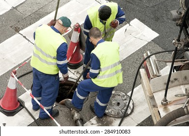 utility service company workers moves the manhole cover to cleaning the sewer line for clogs