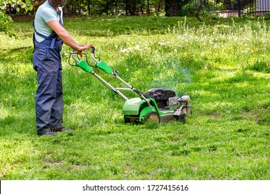 A utility worker in blue overalls looks after a green lawn with a petrol lawnmower.