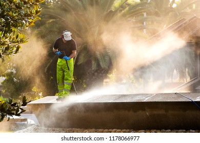 utility worker gardener of municipality service with pressurized water machine  in city park
