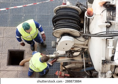 utility  workers moves the manhole cover to cleaning the sewer line for clogs