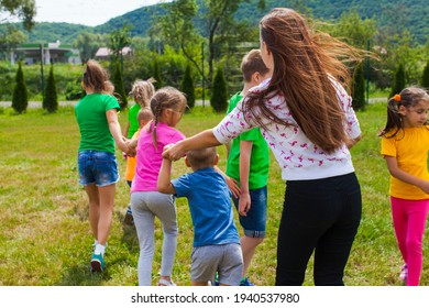 utor with kids play in outdoor games and have fun