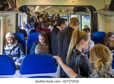 Utrecht, Holland, May 21, 2015; Overcrowded passenger train with most people standing in the aisle