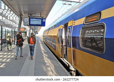 UTRECHT, THE NETHERLANDS, 13 March 2015 - Yellow train of the Dutch railway company Nationale Spoorwegen (NS) arriving at platform.
