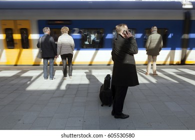 utrecht, netherlands, 15 march 2017: man makes phone call on platform of new central railway station in utrecht while train arrives