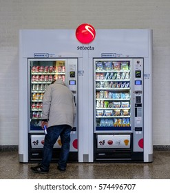 Utrecht, Netherlands, February 2017. man has just bought a can of soft drink from a vending machine with soft drinks and sweet snacks  and is reaching for his change