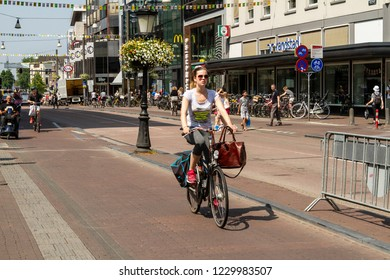 Utrecht, Netherlands - July 6, 2015: Men and women commuting on bicycles on a sunny day in Holland city streets