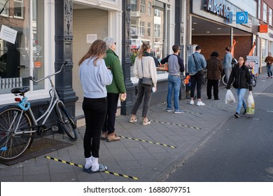 Utrecht, Netherlands - March 28 2020: Social distancing (1.5 meter) at a supermarket entrance during the Corona crisis. The supermarket Albert Heijn is owned and operated by Ahold.