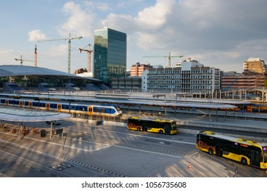 UTRECHT, NETHERLANDS - MAY 21, 2017: Platforms of Utrecht Centraal Railway Station with trains and the bus station with leaving buses on a sunny day.
