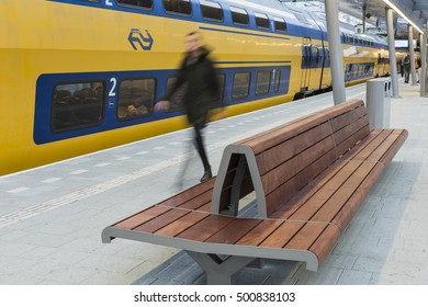 Utrecht, The Netherlands - October 12, 2016: NS Central Railway Station Utrecht with walking people at the platform with train and bench, The Netherlands.