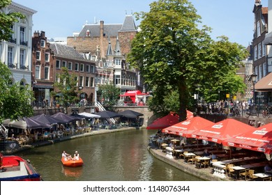 UTRECHT,HOLLAND-August 02,2018:Outdoor cafes alongside the Oude Gracht in Utrecht with a tourist boat in the canal