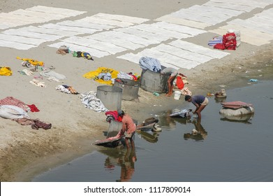 Uttar Pradesh, India -march 7, 2006: Young workers washing clothes in the waters of the Yamuna river next to the city of Agra