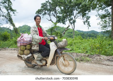 Uttaradit ,Thailand - June 27, 2013 :Farmer is riding a motorcycle  with baskets full of durians at Laplae District ,Uttaradit Province , Thailand